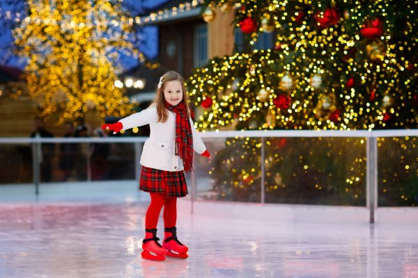 image of young girl on an ice skating rink with holiday lights behind her